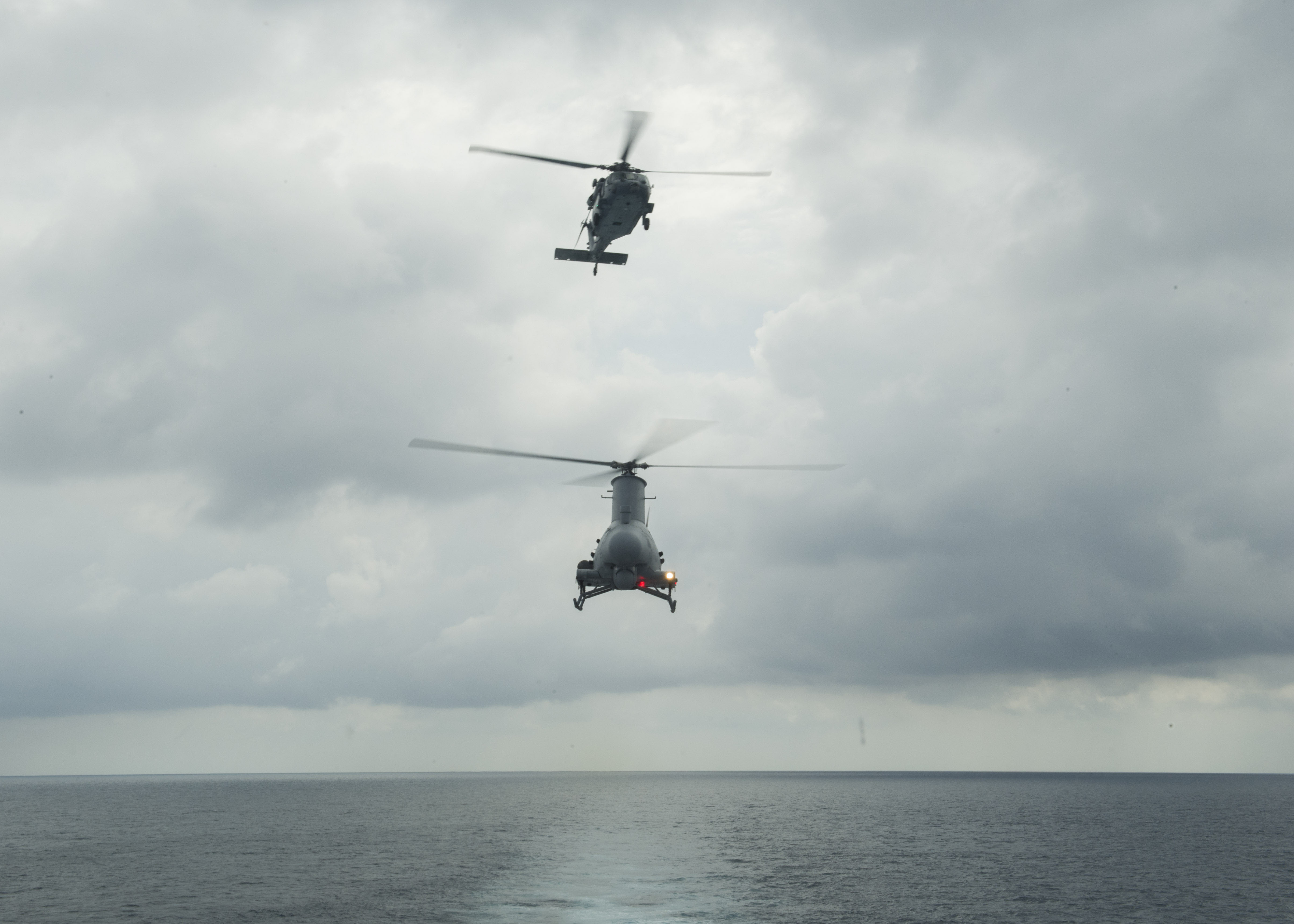 An MH-60S Sea Hawk helicopter, top, and an MQ-8B Fire Scout unmanned helicopter make their approach towards the littoral combat ship USS Coronado (LCS 4) during flight operations. US Navy photo.