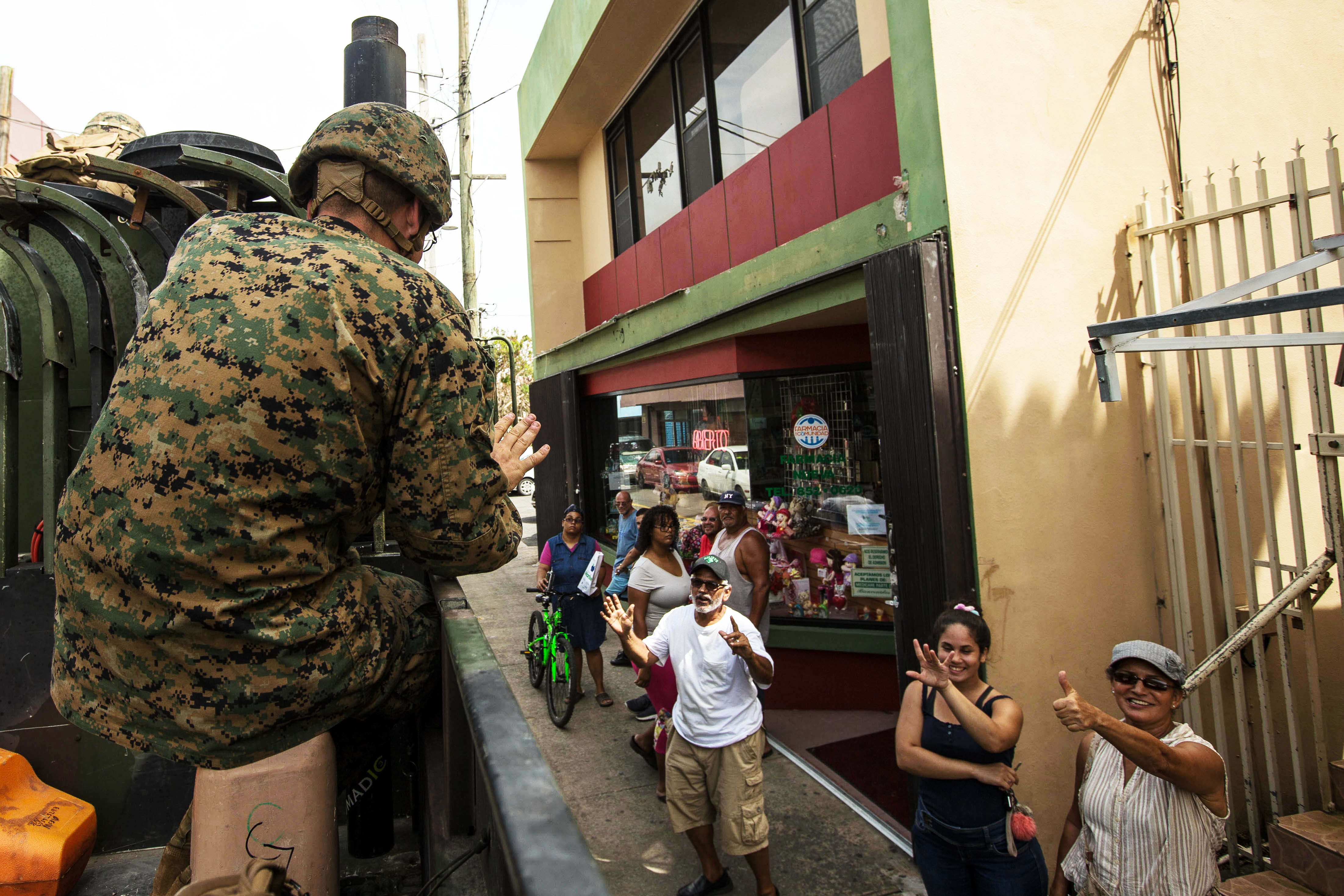 U.S. Marine Corps 1st Lt. Charles V. McCole, an officer with the Air Traffic Control Mobile Team, 26th Marine Expeditionary Unit (MEU), waves to local residents during departure from Humacao Hospital after conducting a medical and operational needs assessment as part of Hurricane Maria relief efforts at Humacao, Puerto Rico, Sept. 27, 2017. (U.S. Marine Corps photo)