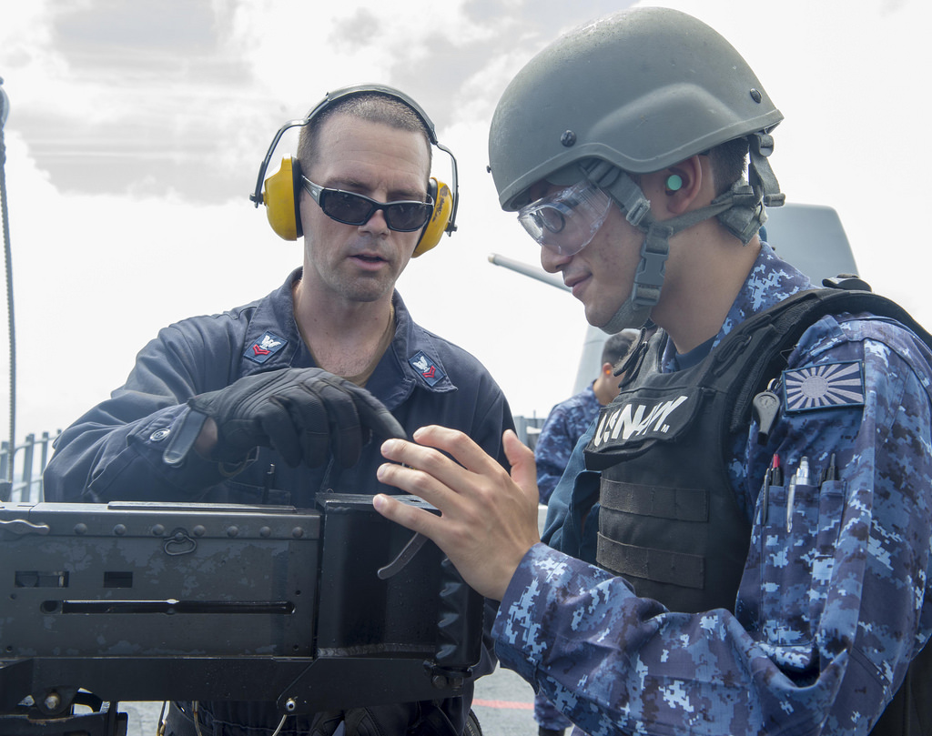 Gunner's Mate 2nd Class Matthew Spano, left, instructs Japan Maritime Self-Defense Force Ensign Taisei Sakai, assigned to JS Kirishima (DDG-174), during a live-fire exercise with a M2HB .50 caliber machine gun aboard USS Antietam (CG-54).