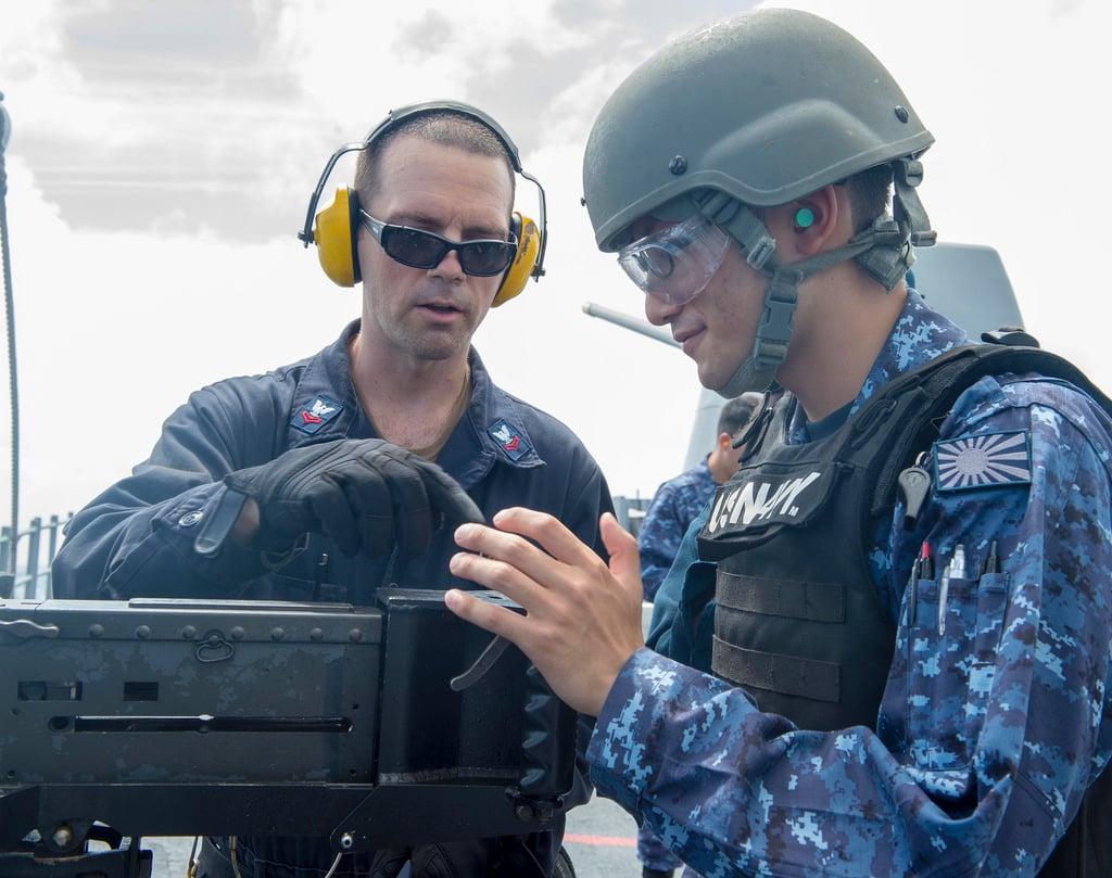Gunner's Mate 2nd Class Matthew Spano, left, instructs Japan Maritime Self-Defense Force Ensign Taisei Sakai, assigned to JS Kirishima (DDG-174), during a live-fire exercise with a M2HB .50 caliber machine gun aboard USS Antietam (CG-54).